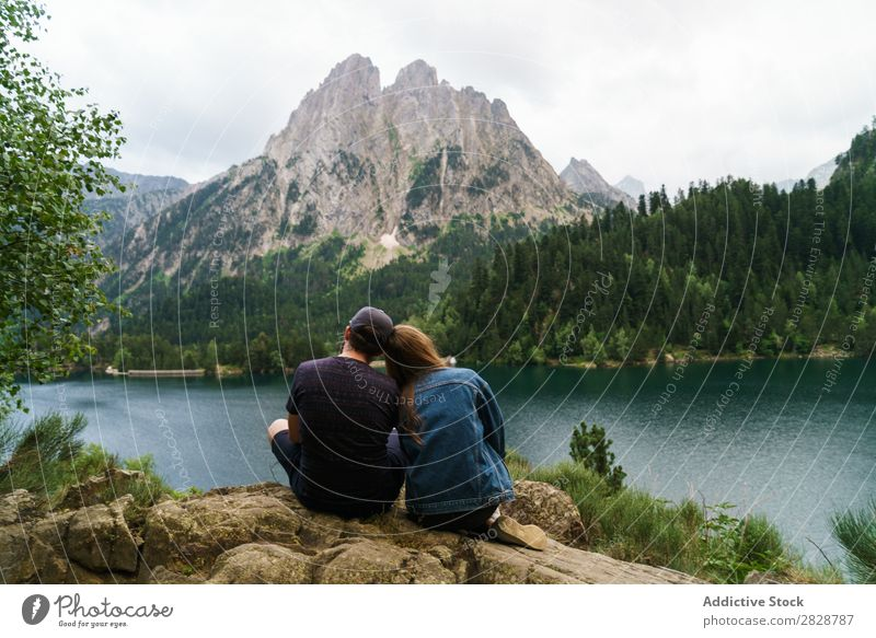 Friends sitting at lake in mountains Woman Man Mountain Together Joy Hiking Lake Water embracing Happy Vacation & Travel Adventure Tourist Youth (Young adults)