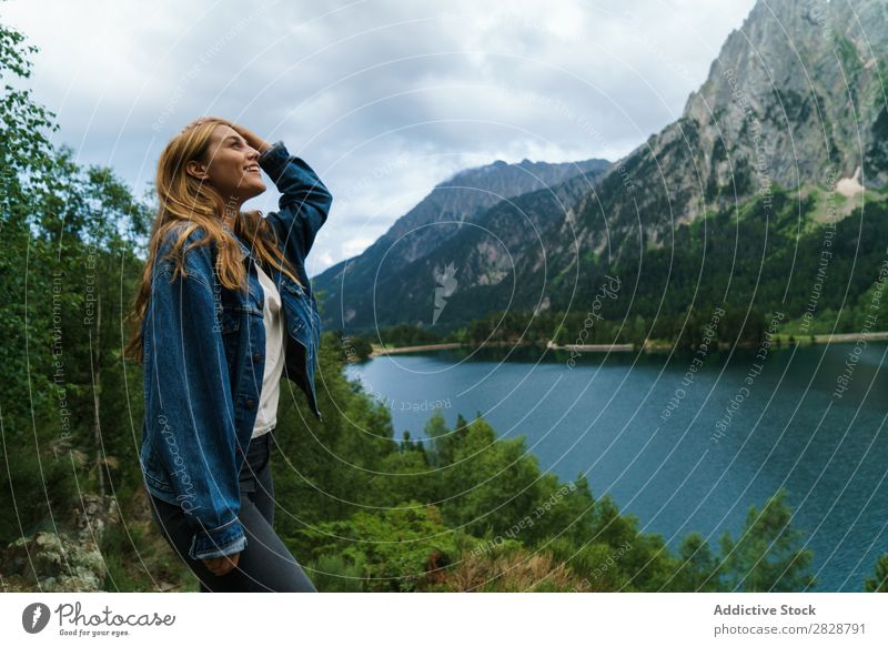 Smiling woman at lake Woman Stone Lake Mountain Nature Landscape Excitement Looking away Water Rock Beautiful Youth (Young adults) Hiking Vacation & Travel