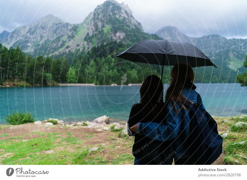 Women under umbrella in mountains Woman Mountain Together Stand Hiking Lake Water Umbrella Rain Cheerful Happy Vacation & Travel Adventure Tourist