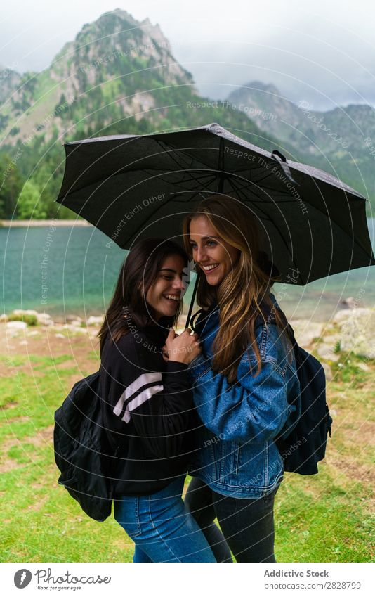 Women under umbrella in mountains Woman Mountain Together Stand Smiling Hiking Lake Water Umbrella Rain Cheerful Happy Vacation & Travel Adventure Tourist