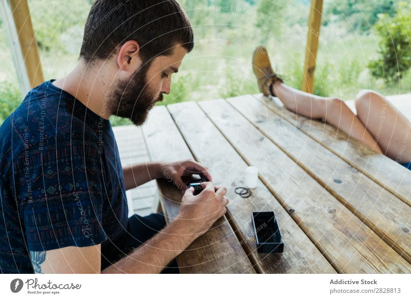 Young man putting new film in camera Man reel photo camera Photographer Nature Creativity Retro Film Camera Vintage Technology Table Sit Relaxation Traveling