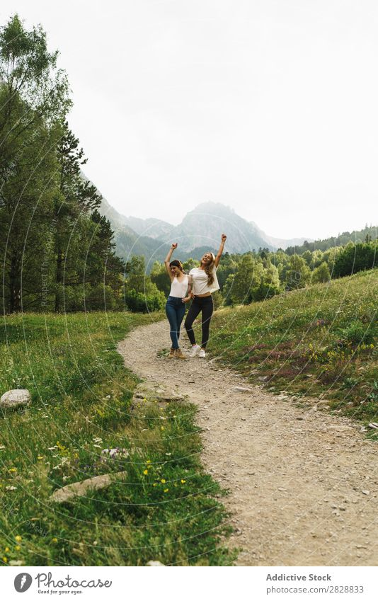 Cheerful women posing on mountain road Woman Walking Street Rural Friendship Backpack Nature Girl Youth (Young adults) Beautiful Vacation & Travel Tourism Trip