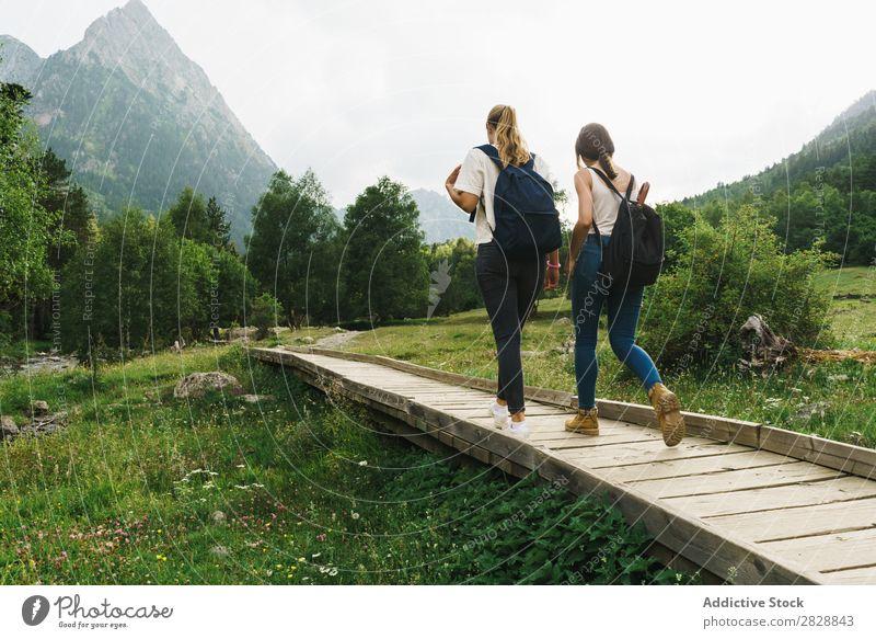 Women walking on wooden path in mountains Woman Walking Street Rural Friendship Backpack Nature