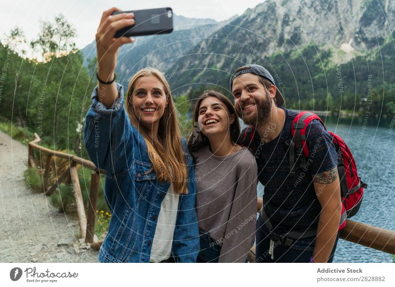 Friends taking selfie in mountains Woman Man Mountain Walking Selfie PDA Take Together Smiling Hiking Lake Water embracing Cheerful Happy Vacation & Travel