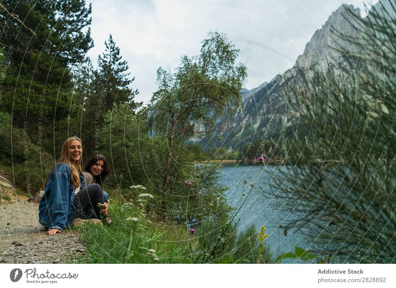Cheerful women sitting at lake Woman Mountain Smiling Sit Together Happy Laughter Hiking Lake Water Vacation & Travel Adventure Tourist Youth (Young adults)