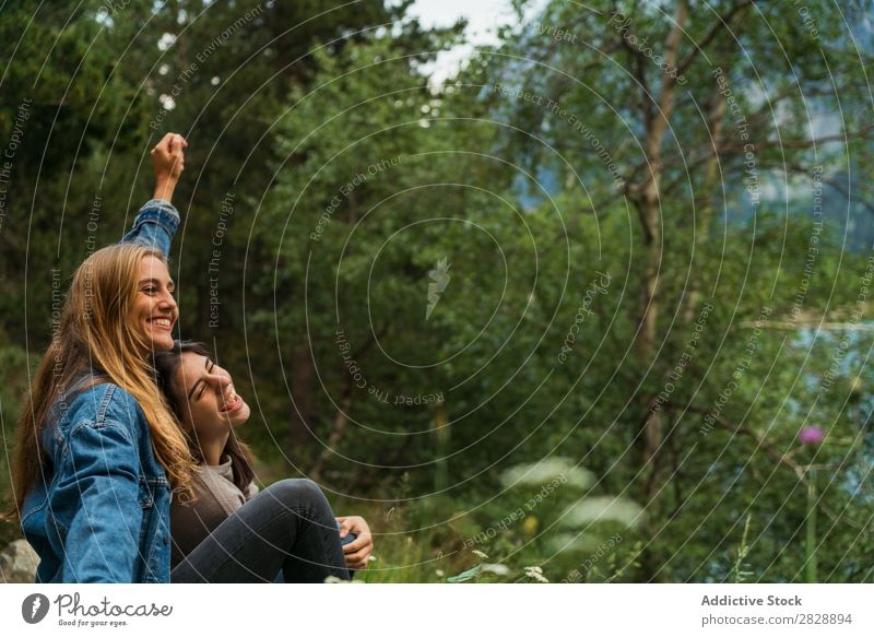 Cheerful women sitting at lake Woman Mountain Smiling Sit Together Happy Laughter Hiking Lake Water embracing Vacation & Travel Adventure Tourist