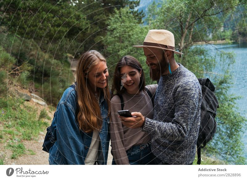 Friends with phone in mountains Woman Man Mountain Walking PDA using browsing Together Smiling Hiking Lake Water Cheerful Happy Vacation & Travel Adventure