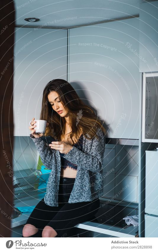 Beautiful model with cup of coffee and smartphone Woman Home Cuddling Coffee Dream human face Posture Cup Pensive Considerate Lifestyle