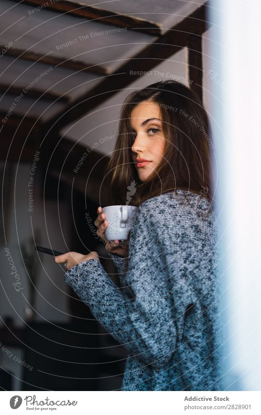 Beautiful model with cup of coffee and smartphone Woman Home Cuddling Coffee Dream Posture Cup Pensive