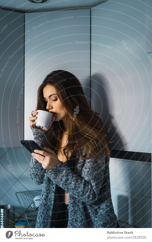 Beautiful model with cup of coffee and smartphone Woman Home Cuddling Coffee Dream human face Posture Cup Pensive Lifestyle House (Residential Structure)