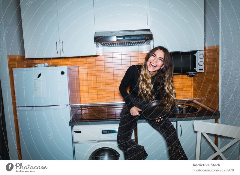 Woman sitting on kitchen table with pan Posture Home Sit Table Kitchen Looking into the camera Beautiful