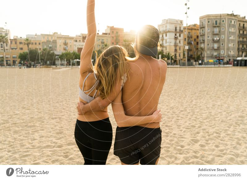 Back view of sportive couple Couple Beach achievement Teamwork Success Athletic Town Gesture Embrace Coast Fitness Landscape City Support shirtless Sportswear