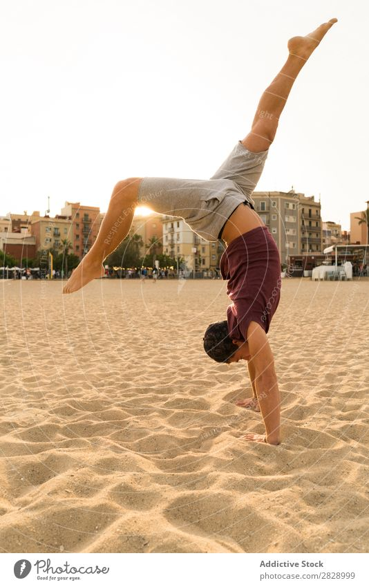 Man In handstand on beach Handstand Beach Sports Practice Fitness Freedom Stand Balance pose Power upside Energy Athlete Easygoing Sunset workout Muscular