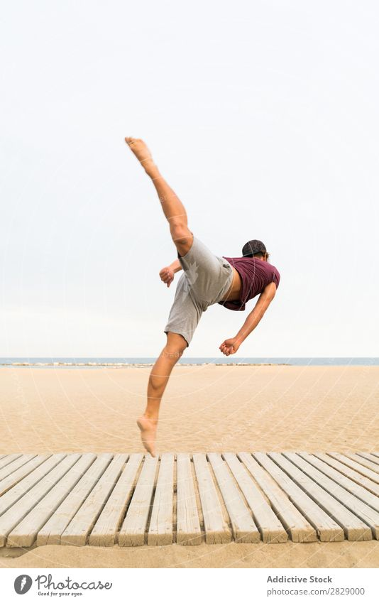 Man practicing jumps on beach Jump Beach Sports flip Practice Fitness Freedom Balance pose Power Energy Athlete Easygoing Sunset workout Muscular Exterior shot