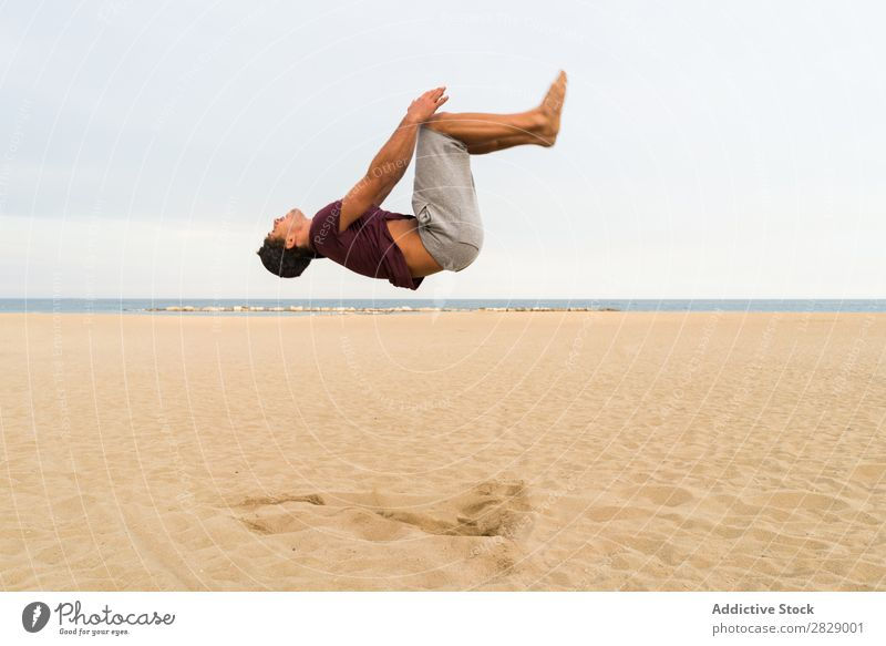 Side view of man in jump Man Beach Athletic flip Jump Sports Practice in motion Fitness Freedom Balance pose Power Energy Athlete Easygoing Sunset workout