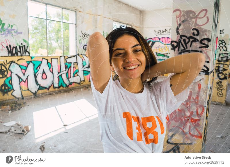 Smiling woman in abandoned room with graffiti Woman Cheerful Posture Looking into the camera Happy Youth (Young adults) Graffiti