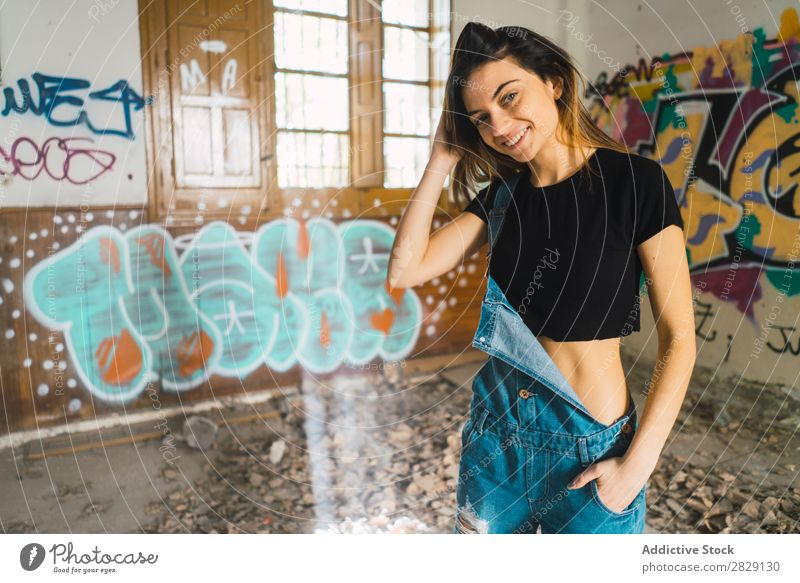 Woman posing in abandoned building Building Smiling Cheerful Posture Graffiti Attractive To enjoy Hair Set Youth (Young adults) Portrait photograph Beautiful