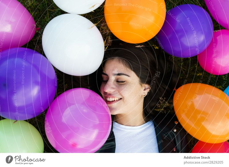 Pretty woman lying in balloons Woman Nature Posture Lie (Untruth) Grass Smiling Laughter Freedom