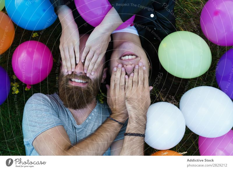Couple in balloons covering eyes Woman Man Together Smiling Love Nature Friendship