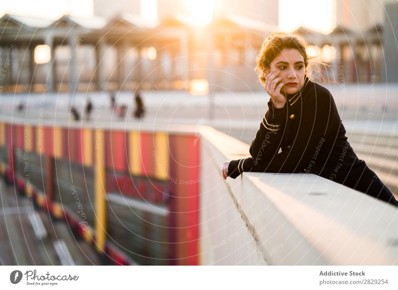 Woman in sunset lights standing at the handrail woman holding head confident looking at camera casual clothes stylish serious young hair female beautiful girl