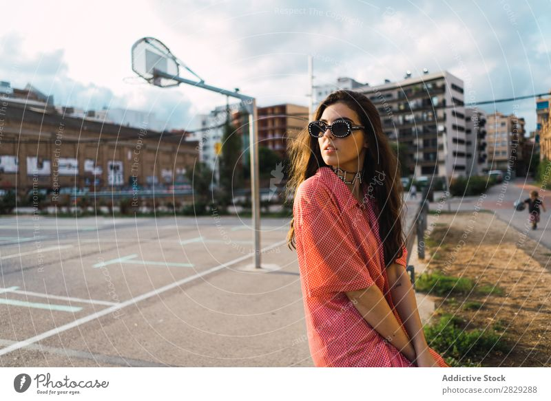 Woman sitting in a fence at playground Style Street Fence Playground Town Posture Sunglasses Portrait photograph Attractive Beauty Photography Hip & trendy