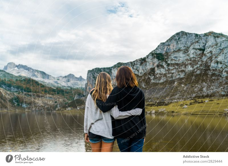 Women standing at lake Woman Meadow Lake embracing Stand Together Friendship Relaxation Mountain Nature Field Girl Grass Beautiful Youth (Young adults) Green