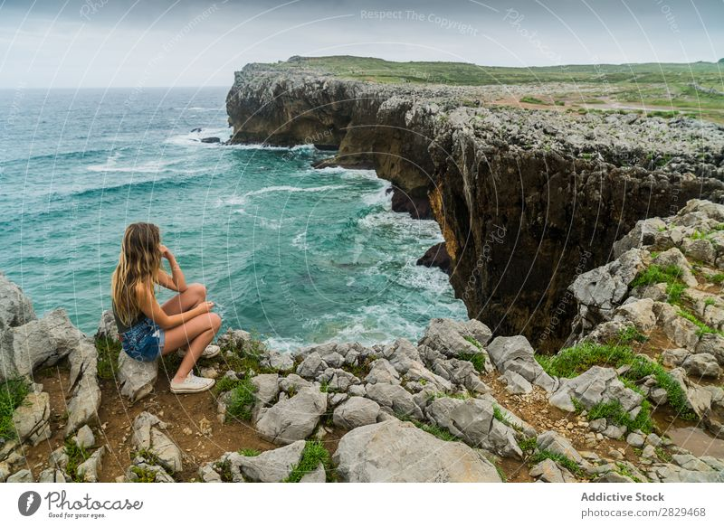 Woman sitting on cliff Cliff Ocean Sit Beautiful Rock Summer Nature Vacation & Travel Water Landscape Youth (Young adults) Blue Lifestyle Freedom Hiking Top