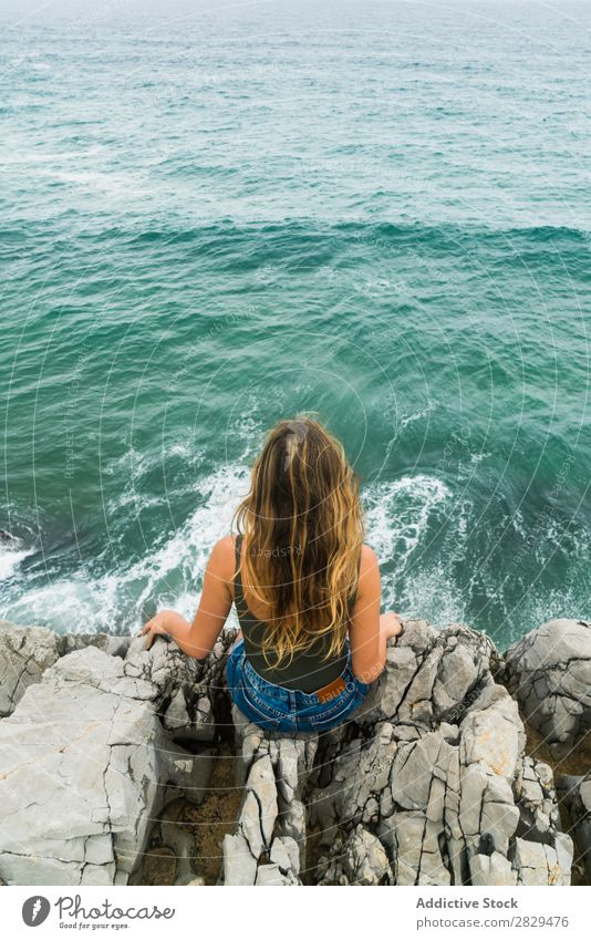 Woman sitting at edge of rock Cliff Ocean Sit Beautiful Rock Summer Nature Vacation & Travel Water Landscape Youth (Young adults) Blue Lifestyle Freedom Hiking