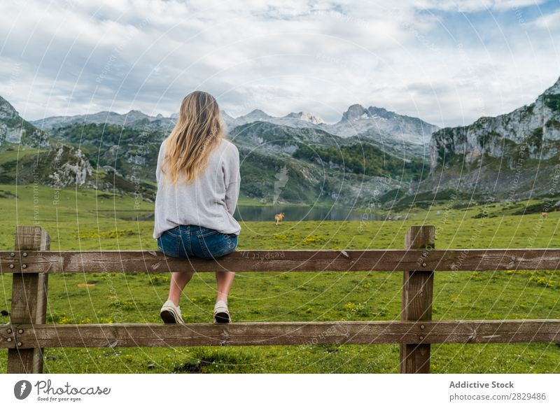 Woman sitting at mountain pasture Meadow Sit Handrail Relaxation Mountain Cow Pasture Nature Field Girl Grass Beautiful Youth (Young adults) Green Spring