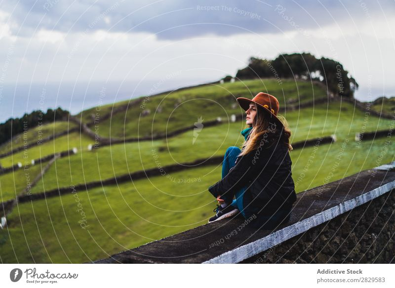 Woman sitting on fence at field Sit Field Green Nature Meadow Fence Relaxation Rest Looking away Hat Spring Summer Grass Landscape Agriculture Rural Sunlight