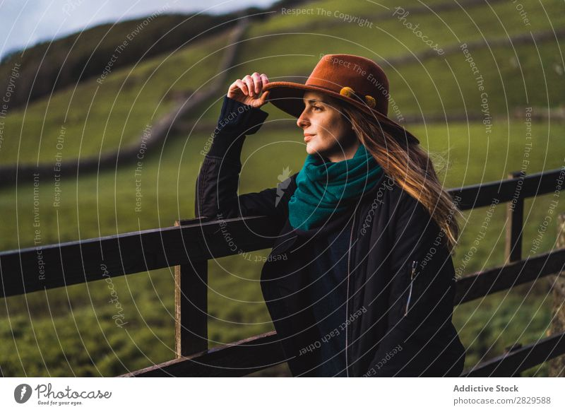 Dreamy woman standing at fence on field Woman Sit Field Green Nature Meadow Fence Stand Relaxation Rest Looking away Hat Spring Summer Grass Landscape