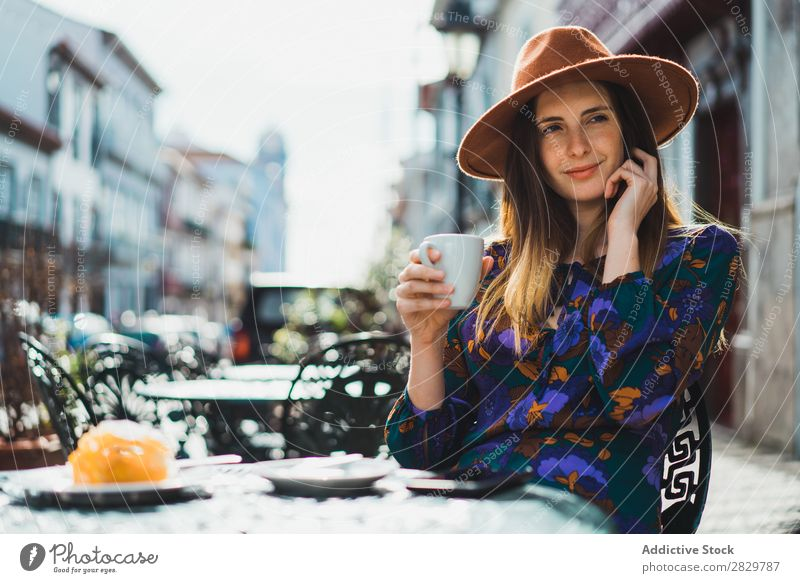 Woman with cup and smartphone in outside cafe pretty Style Street Hat Coffee Cup Café Exterior shot Fashion Beautiful Youth (Young adults) Portrait photograph