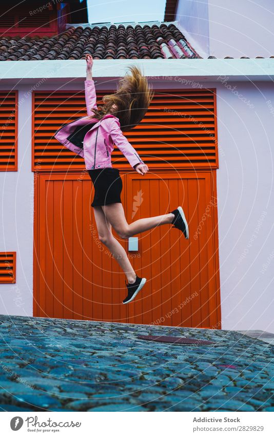 Stylish girl flying above ground Woman Jump Flying Movement Street up Beauty Photography waving hair romantic Town Expression City Style Happiness Jacket