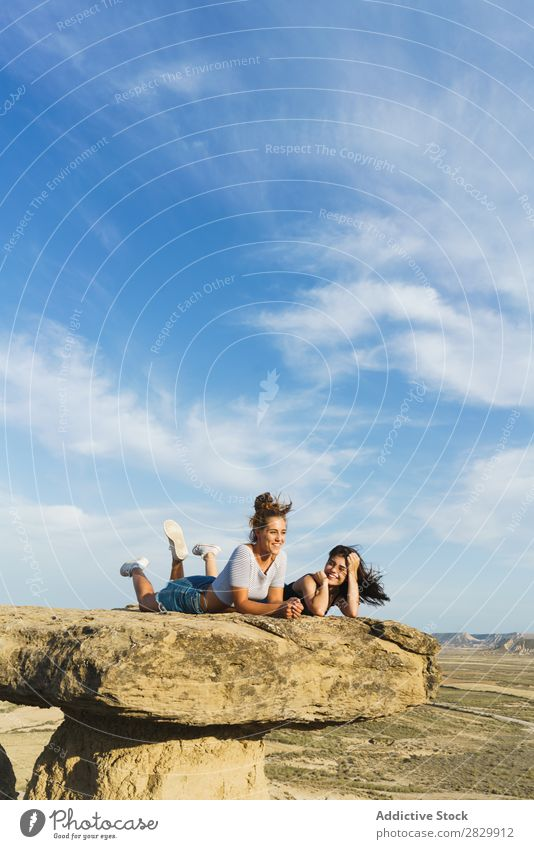 Excited women lying on cliff Woman Cliff Lie (Untruth) Relaxation Vacation & Travel Adventure Rock Mountain Tourist Friendship Together Smiling Happy Excitement