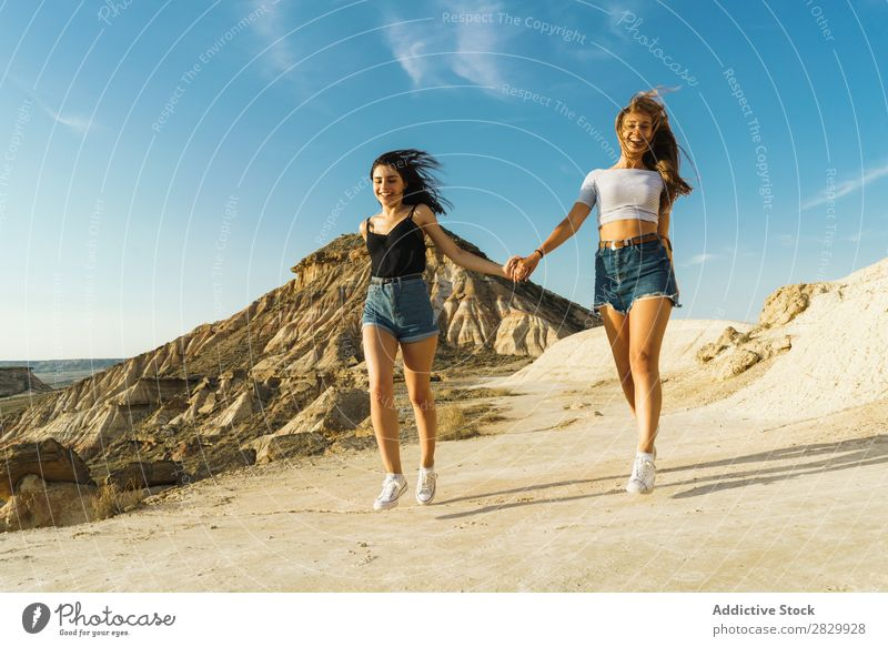Happy women walking on hill Woman Cliff Excitement Running holding hands Freedom Vacation & Travel Success Top Mountain Youth (Young adults) Nature Rock