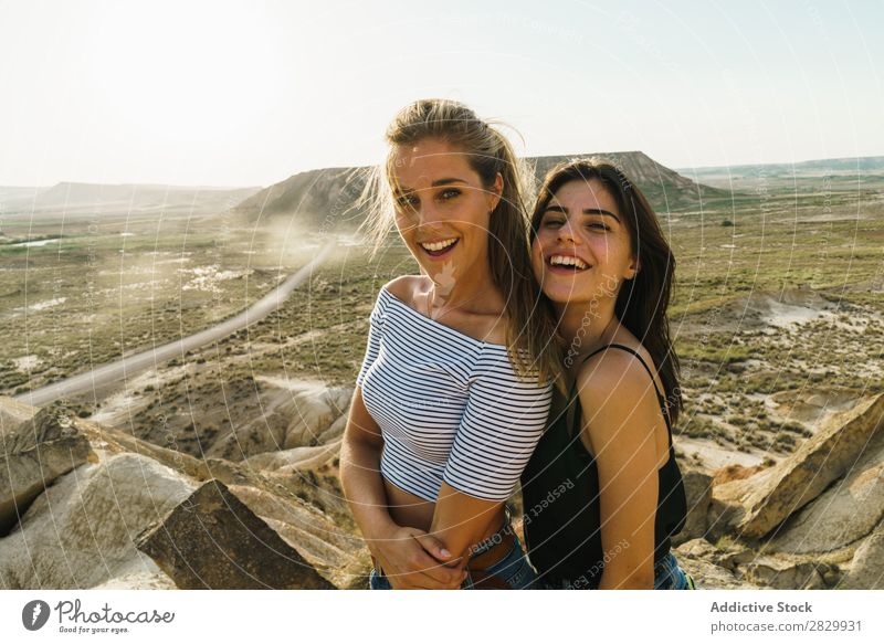 Cheerful women standing on cliff Woman Cliff Excitement embracing Looking into the camera Smiling Embrace Freedom Vacation & Travel Success Top Mountain
