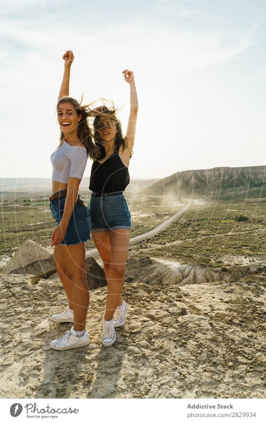 Cheerful women standing on cliff Woman Cliff Excitement Looking into the camera Smiling Embrace Freedom Vacation & Travel Success Top Mountain