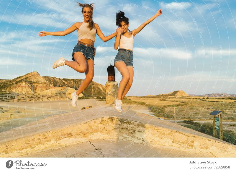 Happy women jumping on hill Woman Cliff Excitement holding hands Freedom Vacation & Travel Success Top Mountain Youth (Young adults) Nature Rock Landscape
