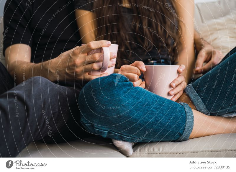 Crop couple with cups Couple Home Together Sit embracing Cup Drinking Beverage Sofa Couch Cozy Human being Happy Love House (Residential Structure) Man Woman