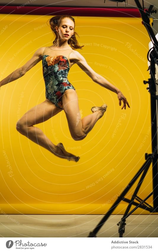 Woman jumping in studio pretty Portrait photograph Youth (Young adults) Jump Ballet Dance Beautiful Adults Posture Smiling Beauty Photography Attractive Model