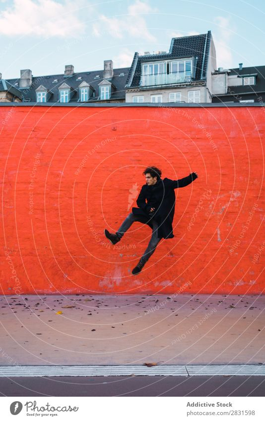 Man jumping at orange wall handsome City Street Jump Wall (building) Orange Joy Trick Youth (Young adults) Town Lifestyle Easygoing Fashion Style Adults Modern