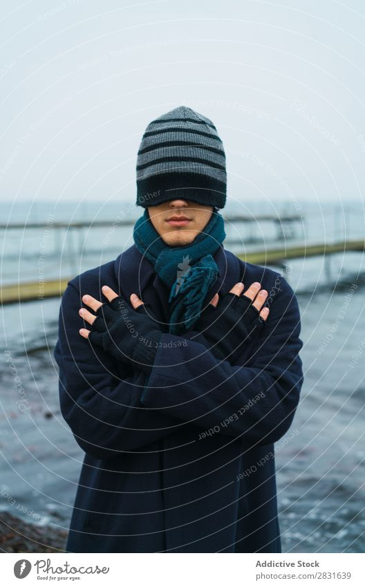 Man putting on hat on eyes Style seaside Cold Coat warm clothes Hat Adjust Ocean Nature Youth (Young adults) Adults Blue Vacation & Travel Water Guy Modern