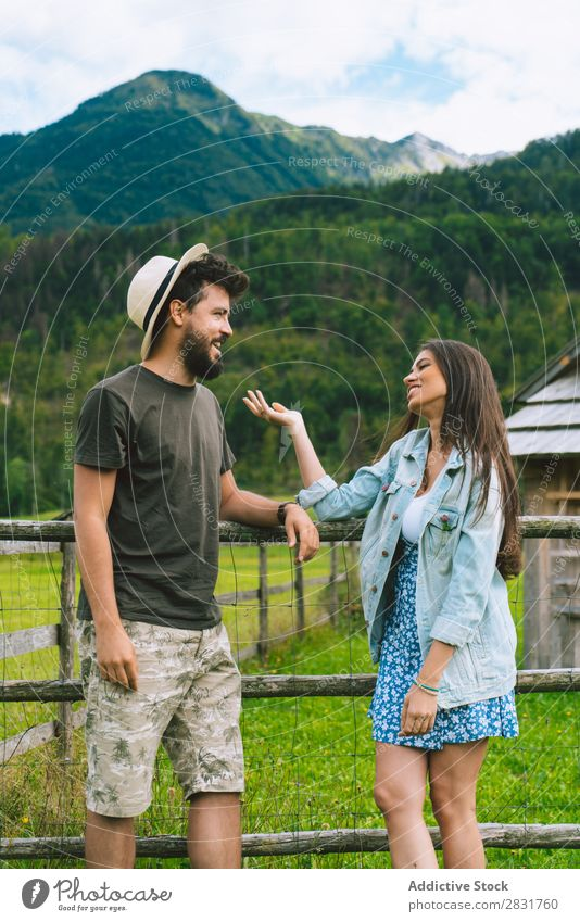 Couple speaking on meadow Hat Hill Nature Summer Human being Man Woman Love Grass Beautiful Together Youth (Young adults) Happy Landscape Vacation & Travel