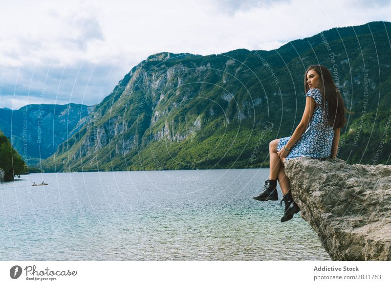 Woman sitting on stone at lake Lake Mountain Stone Sit Nature Summer Water Youth (Young adults) Vacation & Travel Lifestyle Human being Beautiful Landscape Girl
