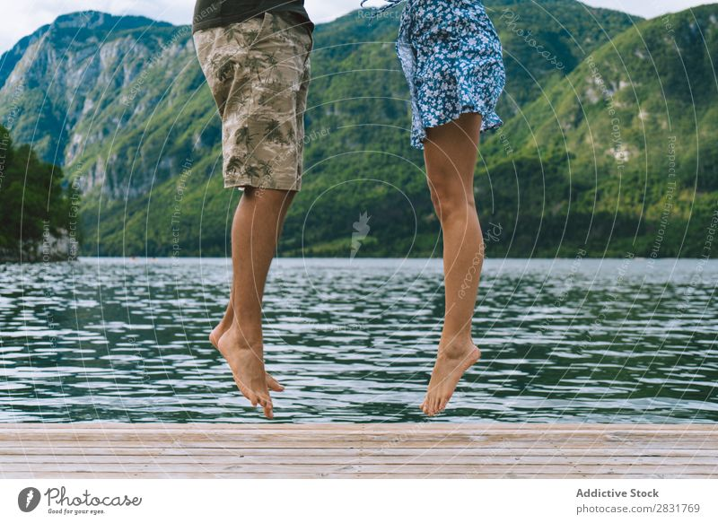Crop couple posing on pier Couple Jetty Joy Lake Mountain Jump Happy Love Together Nature Summer Water Youth (Young adults) Woman Vacation & Travel Lifestyle