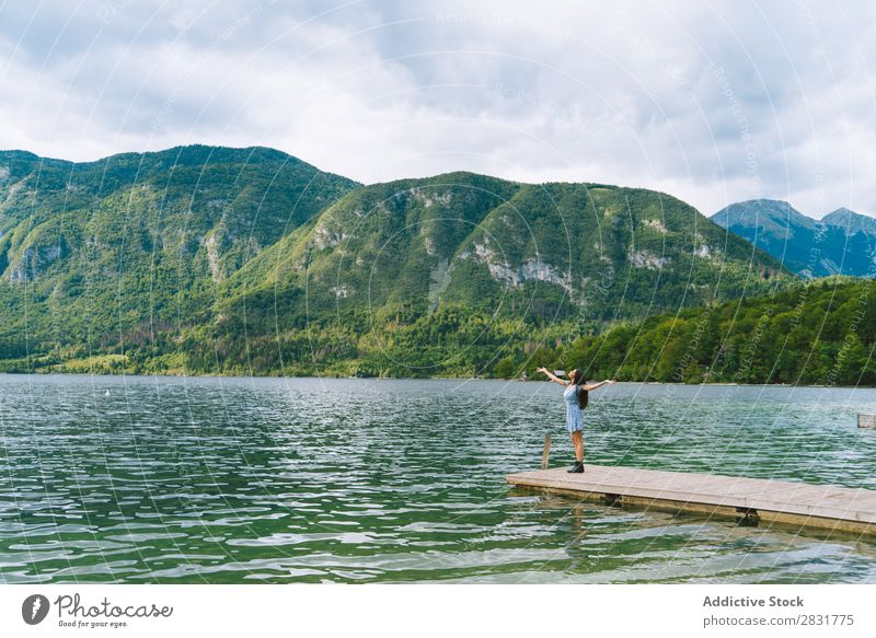 Woman on pier at lake Lake Mountain Jetty hands apart Nature Summer Water Youth (Young adults) Vacation & Travel Lifestyle Human being Beautiful Landscape Girl