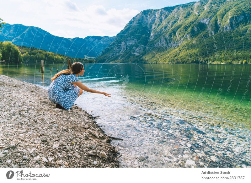 Woman sitting at lake Lake Hand pulling Coast Sit Mountain Nature Summer Water Youth (Young adults) Vacation & Travel Lifestyle Human being Beautiful Landscape