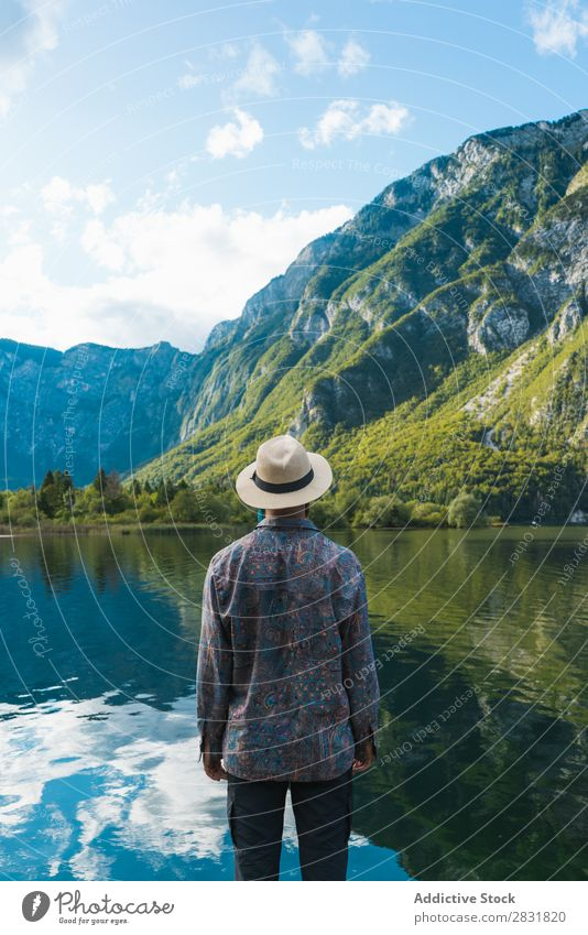 Man standing at lake Lake Stand Mountain Water Nature Landscape Human being Tourism Hiking Loneliness Calm Tourist Rock scenery Relaxation Freedom