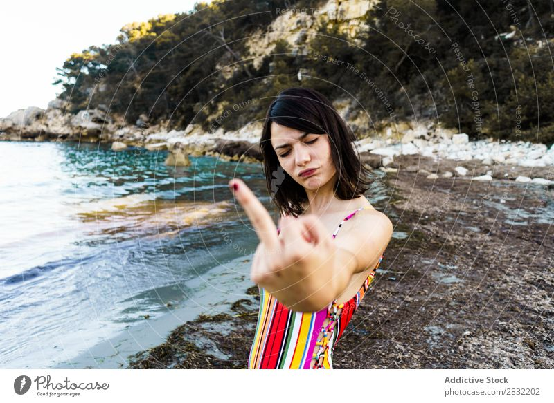 Expressive girl on beach showing middle finger Woman Beach Gesture provocation Aggressive Summer abusive Emotions Youth (Young adults) Vacation & Travel