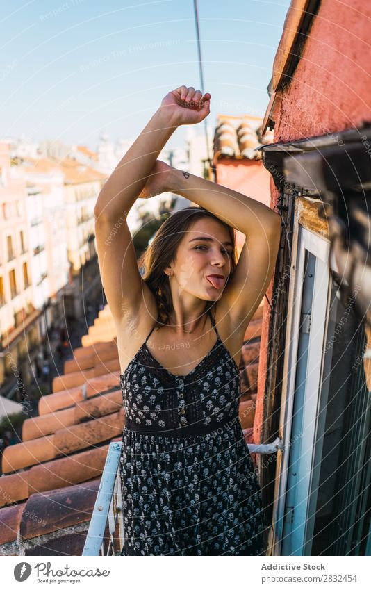 Content model grimacing on balcony Woman Cheerful romantic Happiness Grimace showing tongue Skyline Balcony Terrace Posture Expression Beauty Photography